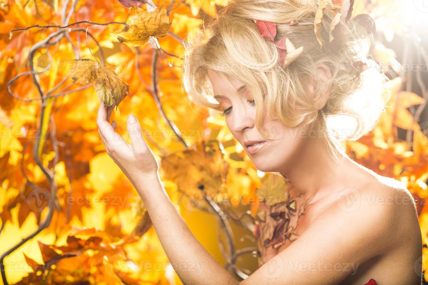 magisches goldenes Herbstblondes Mädchenporträt in Blättern foto