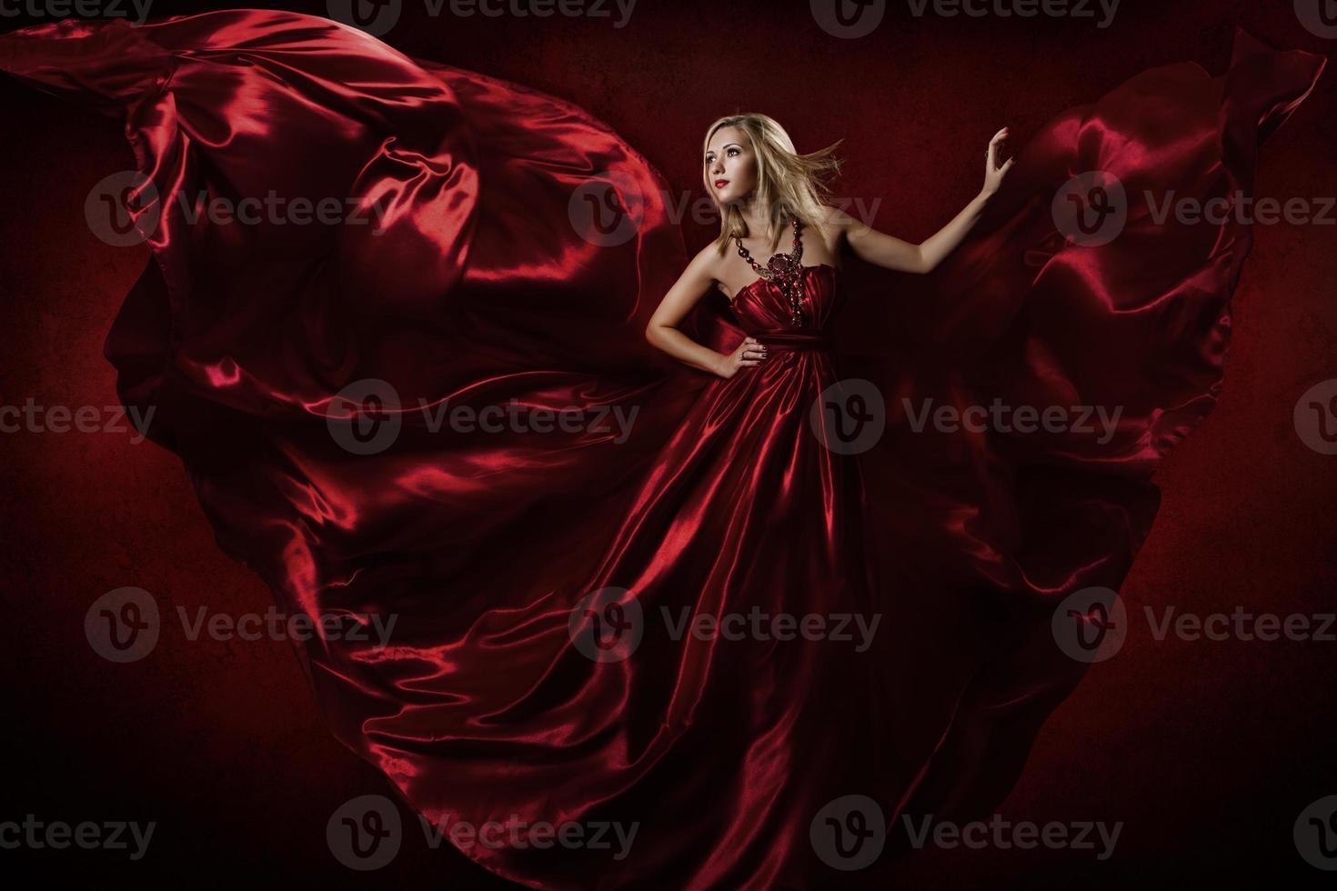 Frau im roten Kleid tanzt mit fliegendem Stoff foto