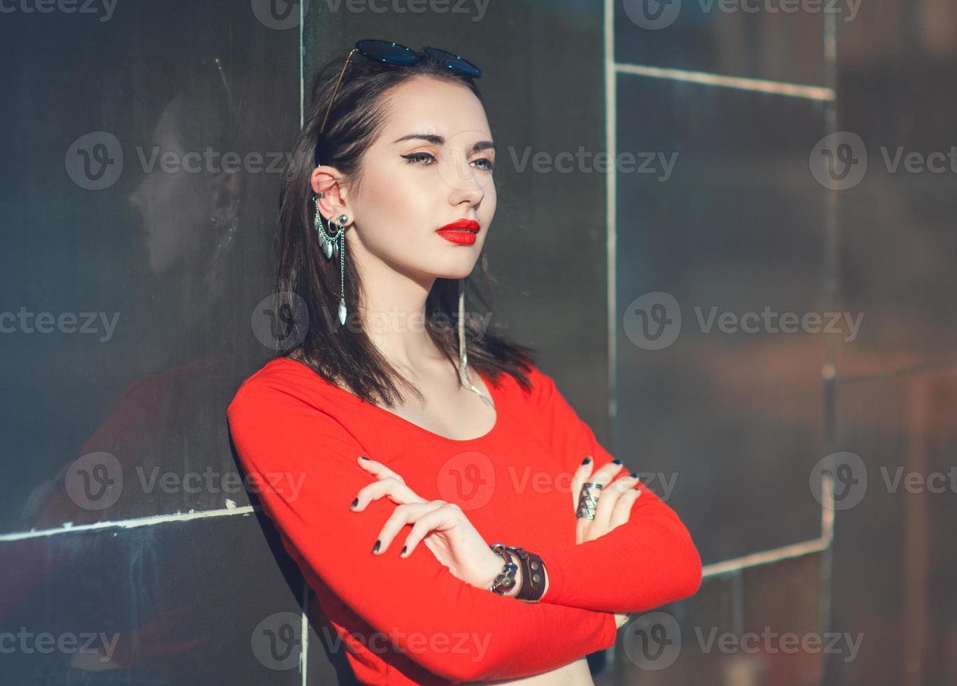 junges schönes Hipster-Mädchen in der roten Bluse mit Sonnenbrille foto
