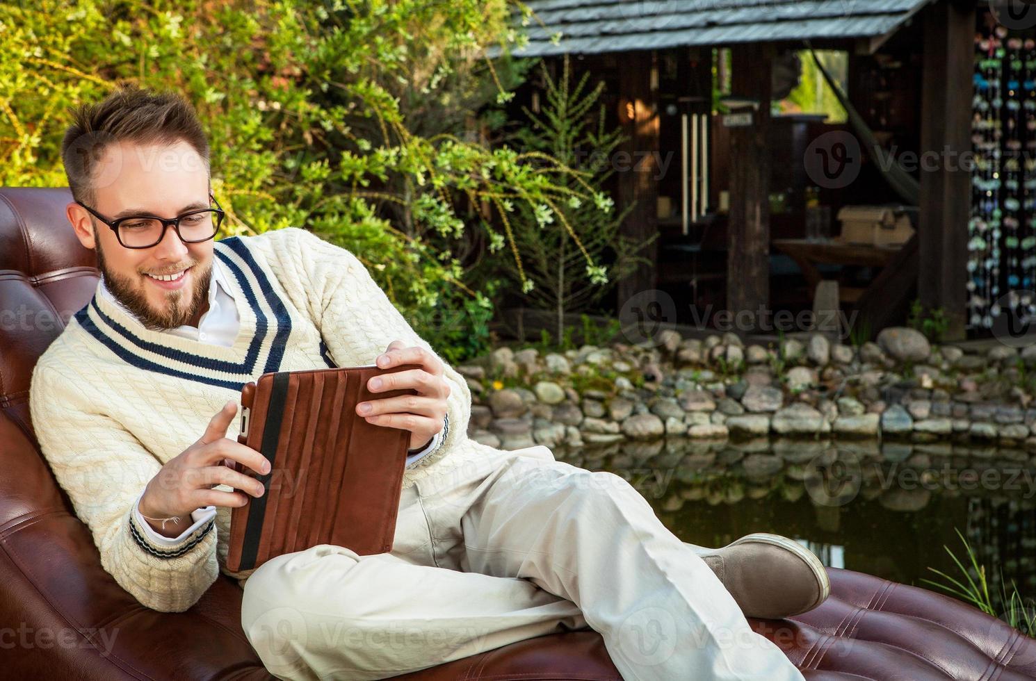 schöner Mann sitzen im Sofa mit iPad im Sommergarten. foto