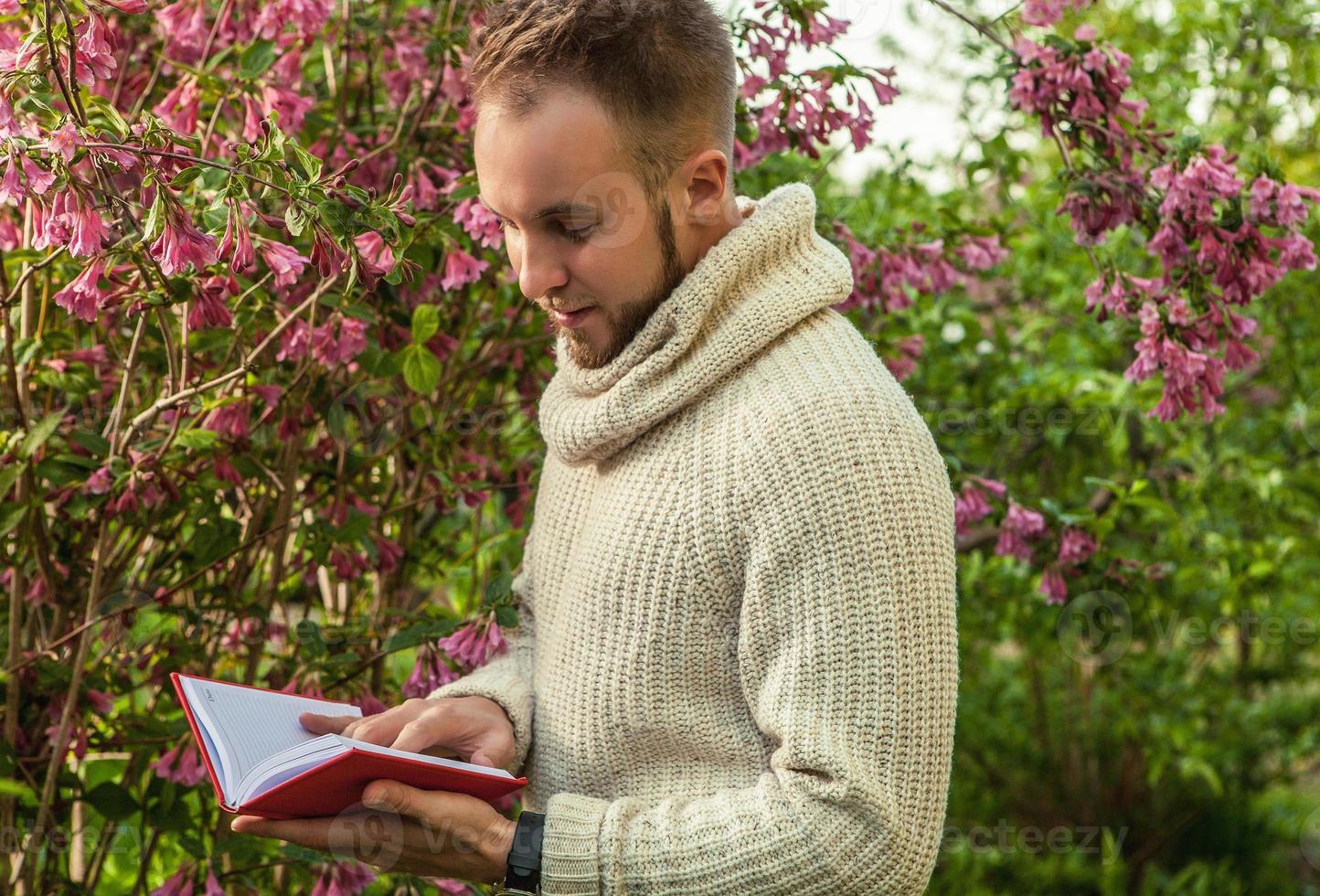 junger freundlicher Mann mit rotem Buch in einem Sommergarten. foto