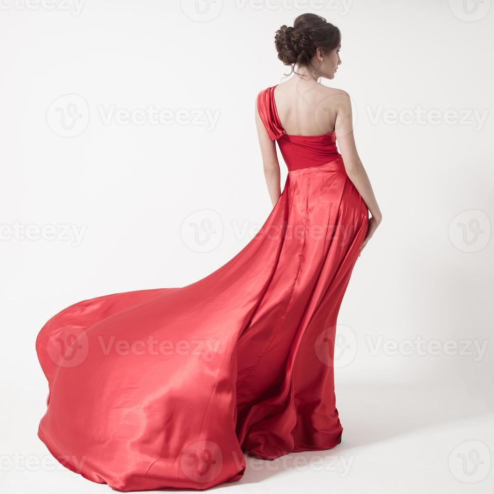 junge Schönheitsfrau im flatternden roten Kleid. weißer Hintergrund. foto