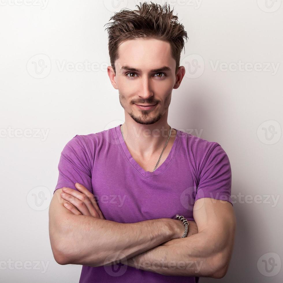 Porträt des jungen gutaussehenden Mannes im violetten T-Shirt. foto