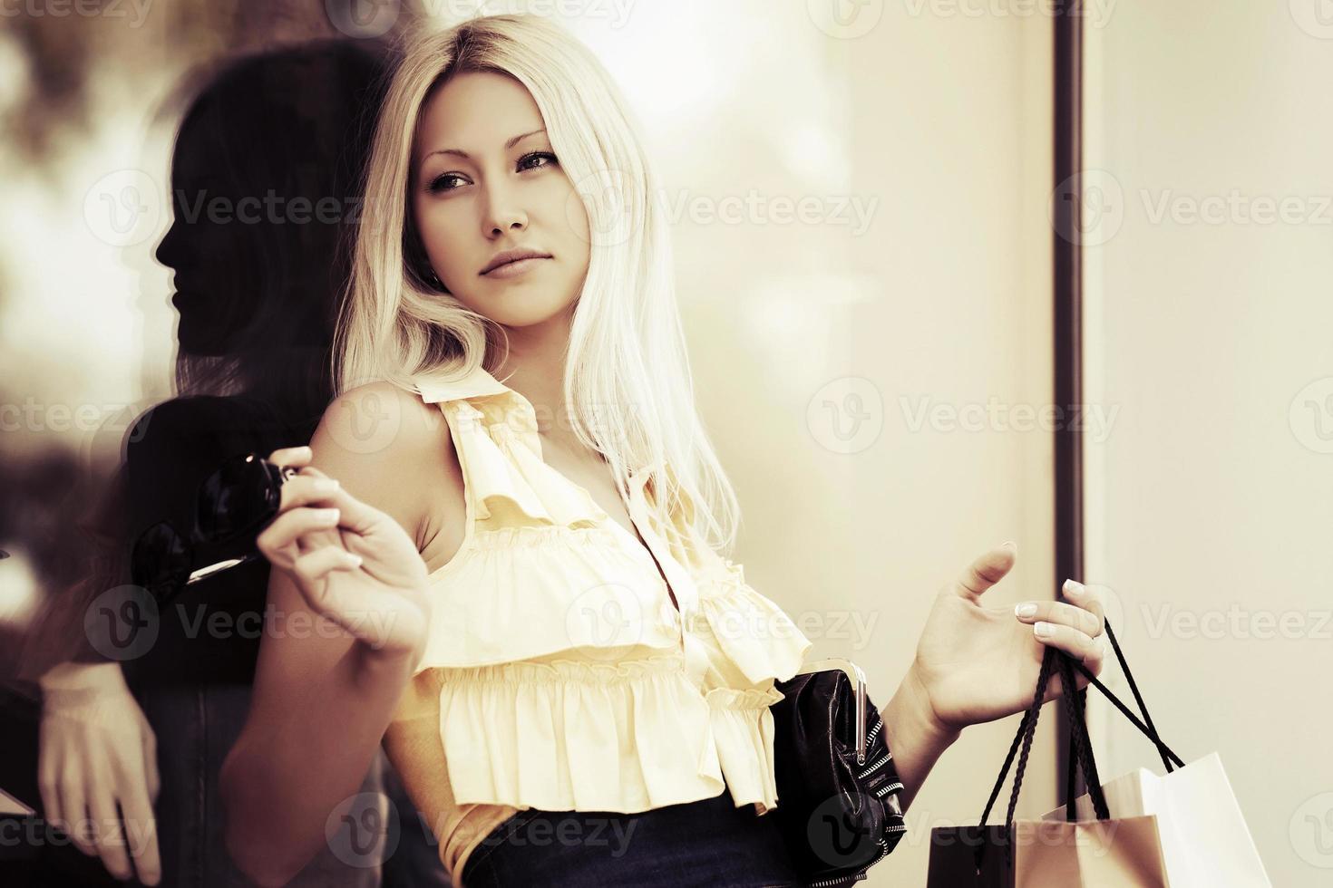 junge Modefrau mit Einkaufstüten am Einkaufszentrumfenster foto
