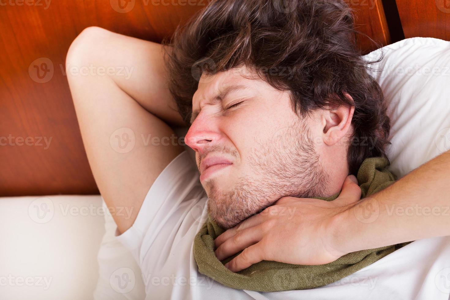 junger Mann mit Halsschmerzen foto