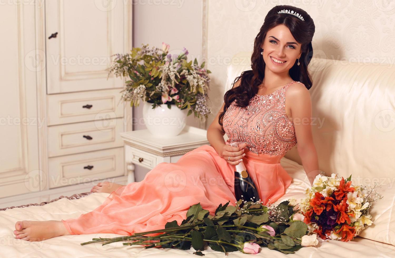 schöne lächelnde Braut, die Flasche Champagner hält foto
