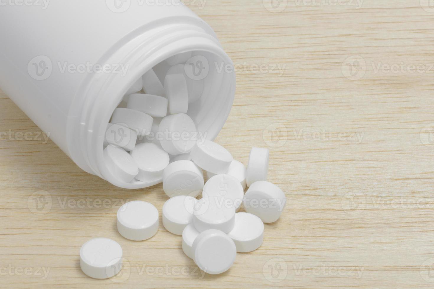 Pillen, die aus der Pillenflasche auf Holzhintergrund verschüttet werden foto