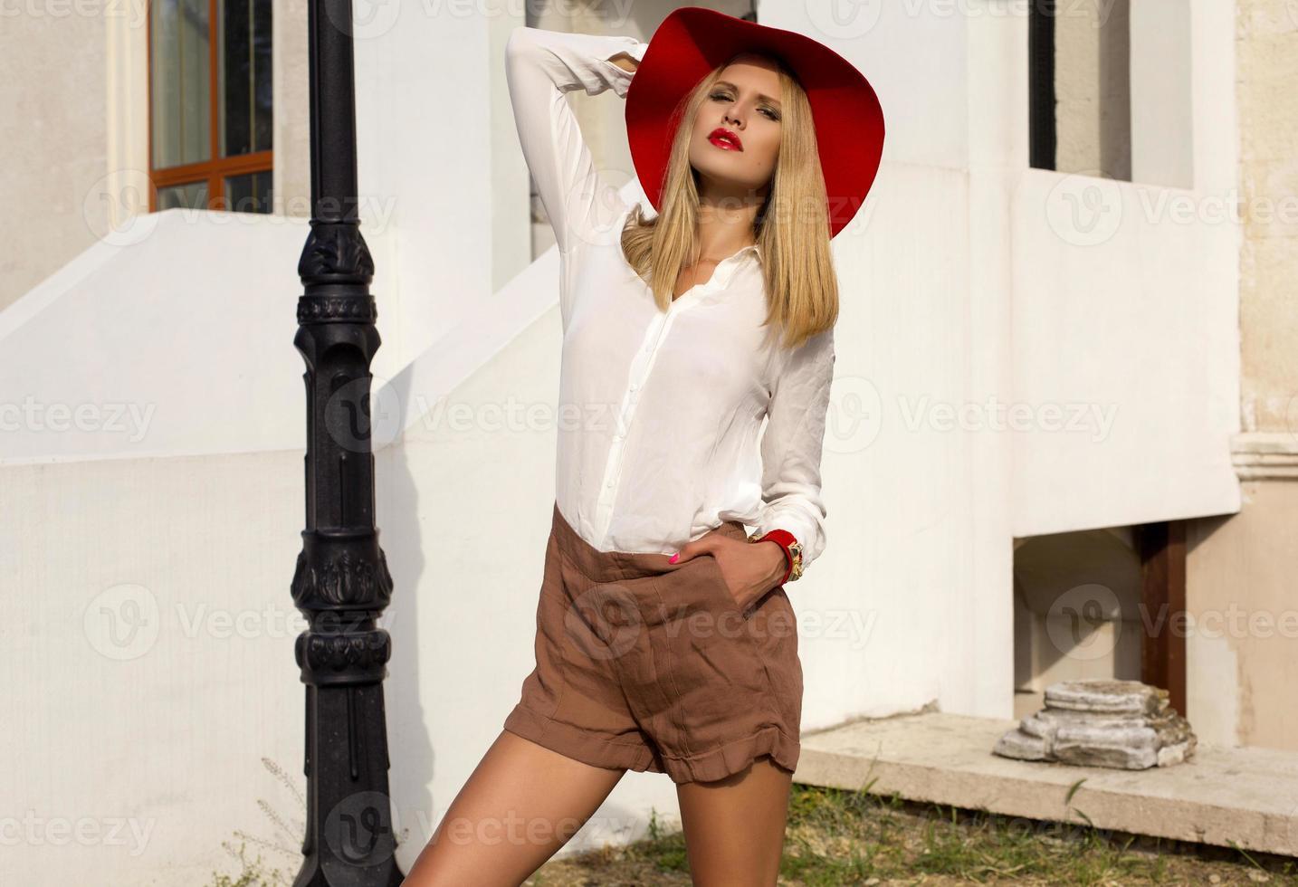 Mädchen mit blonden Haaren in elegantem rotem Hut und Hemd foto