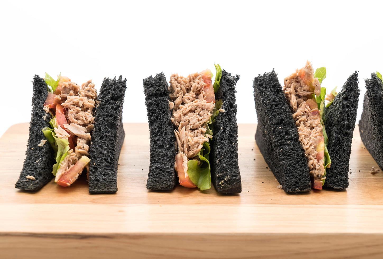 Thunfisch-Holzkohle-Sandwiches auf Schneidebrett foto