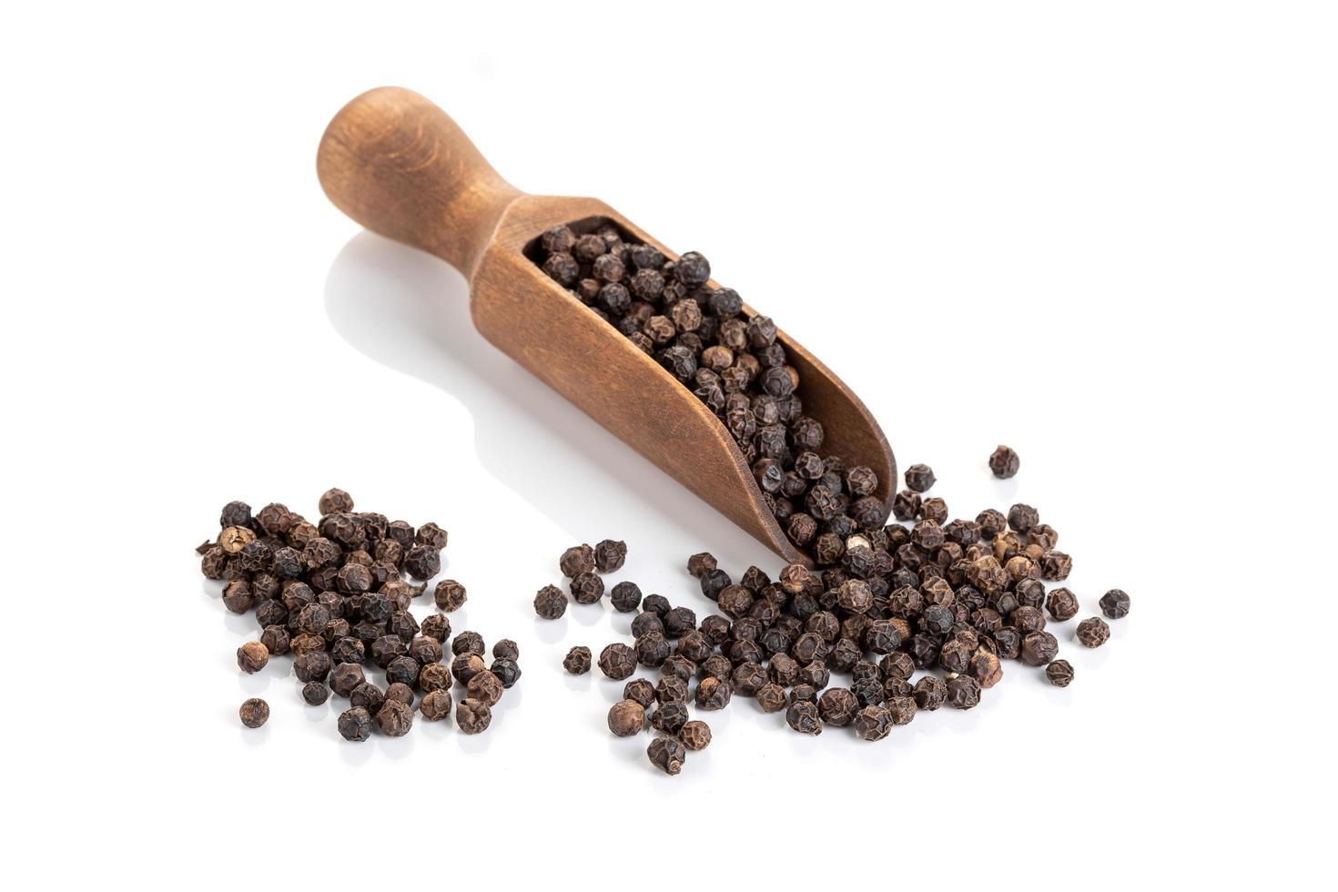 schwarze Pfefferkerne in einer Holzschaufel foto
