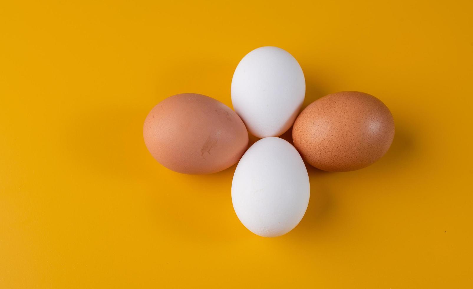 vier Eier auf gelbem Hintergrund foto