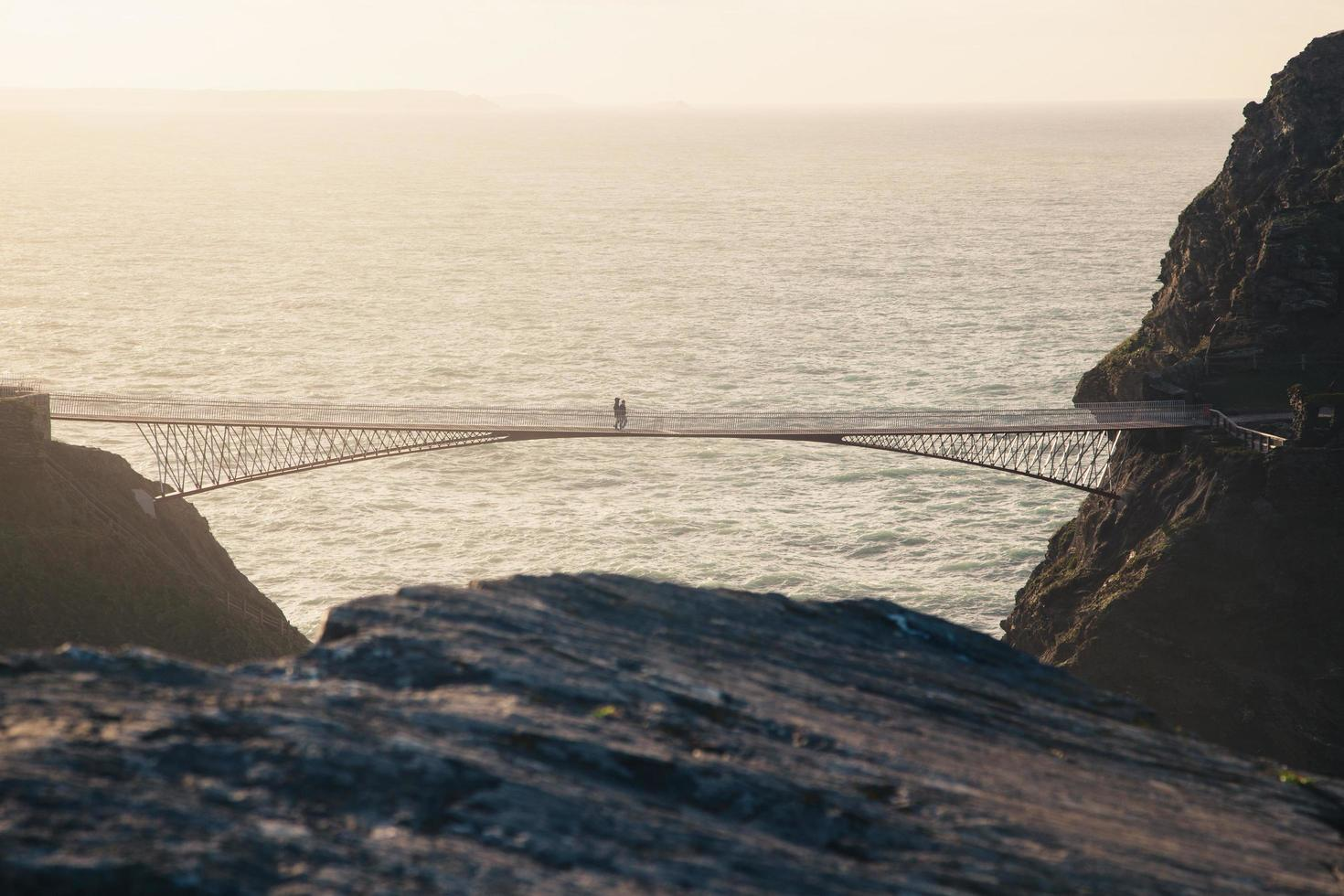 Leute, die zur goldenen Stunde auf einer Brücke gehen foto