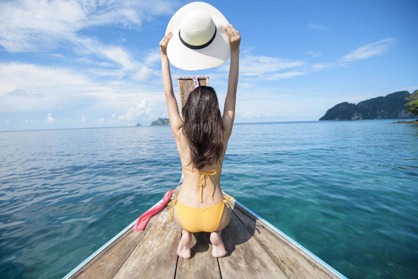 Frau hält Hut auf einem Boot foto