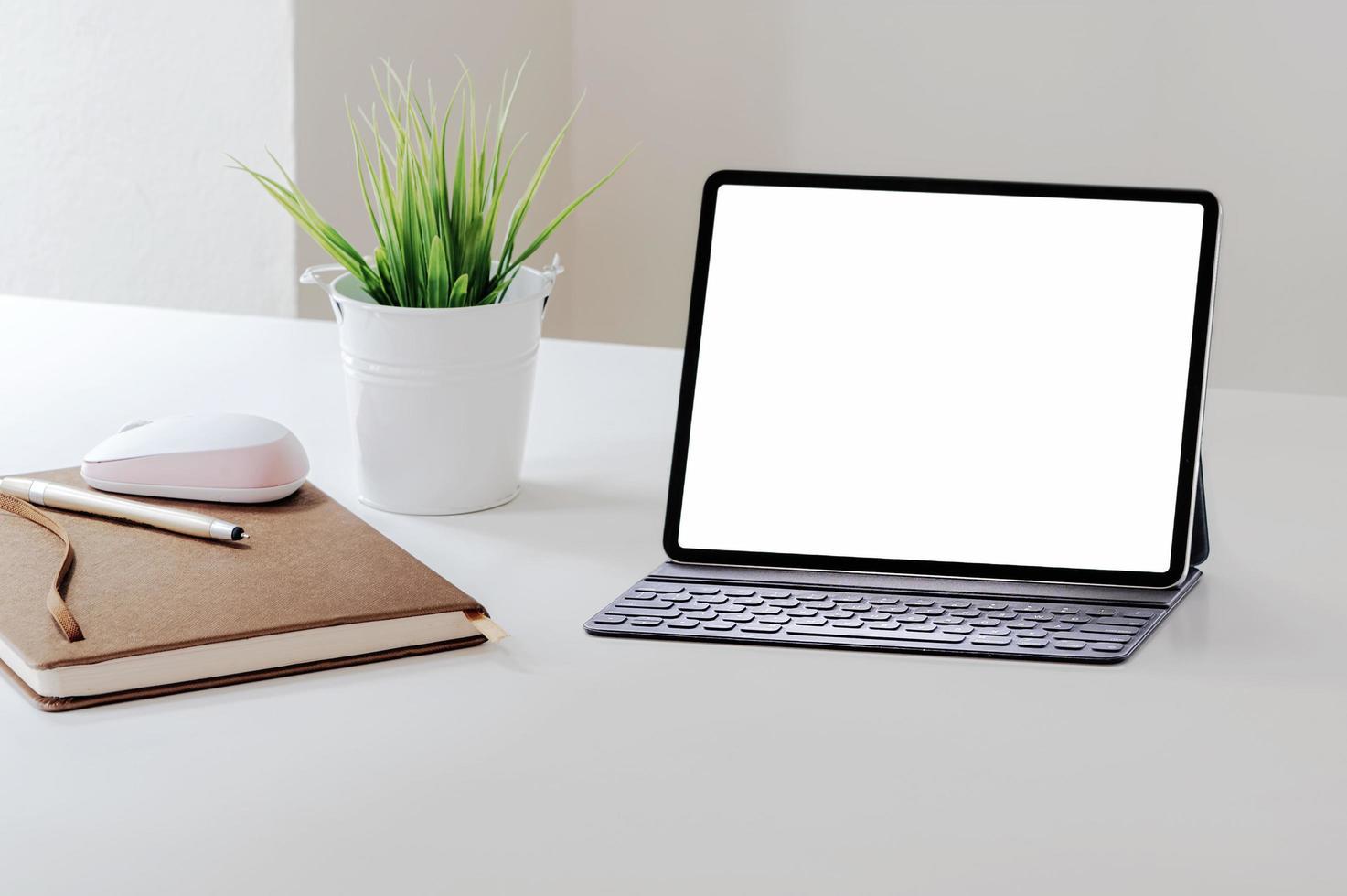Tablette mit Tastaturmodell auf weißem Tisch foto