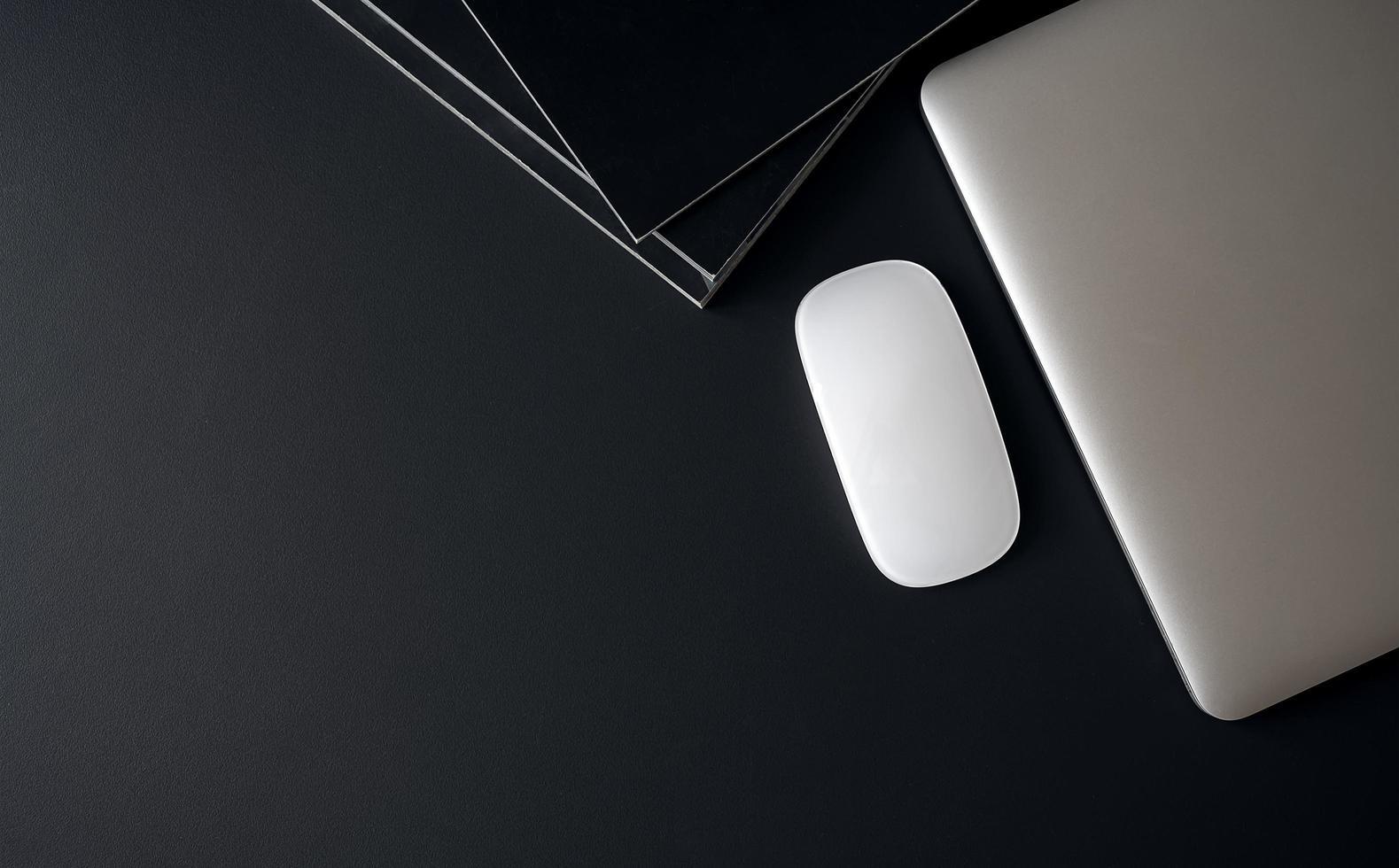 Draufsicht des Laptops mit Maus und Büchern auf schwarzem Tisch foto