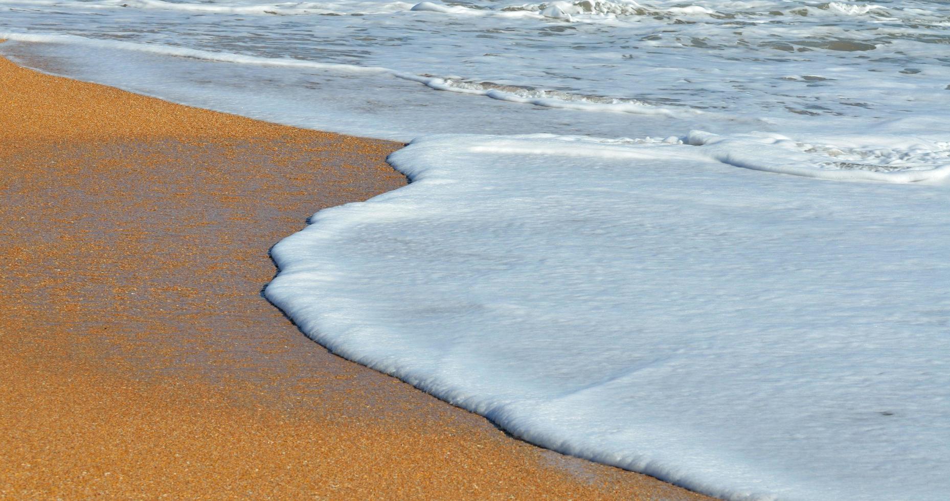 weißer Schaum am Strand foto
