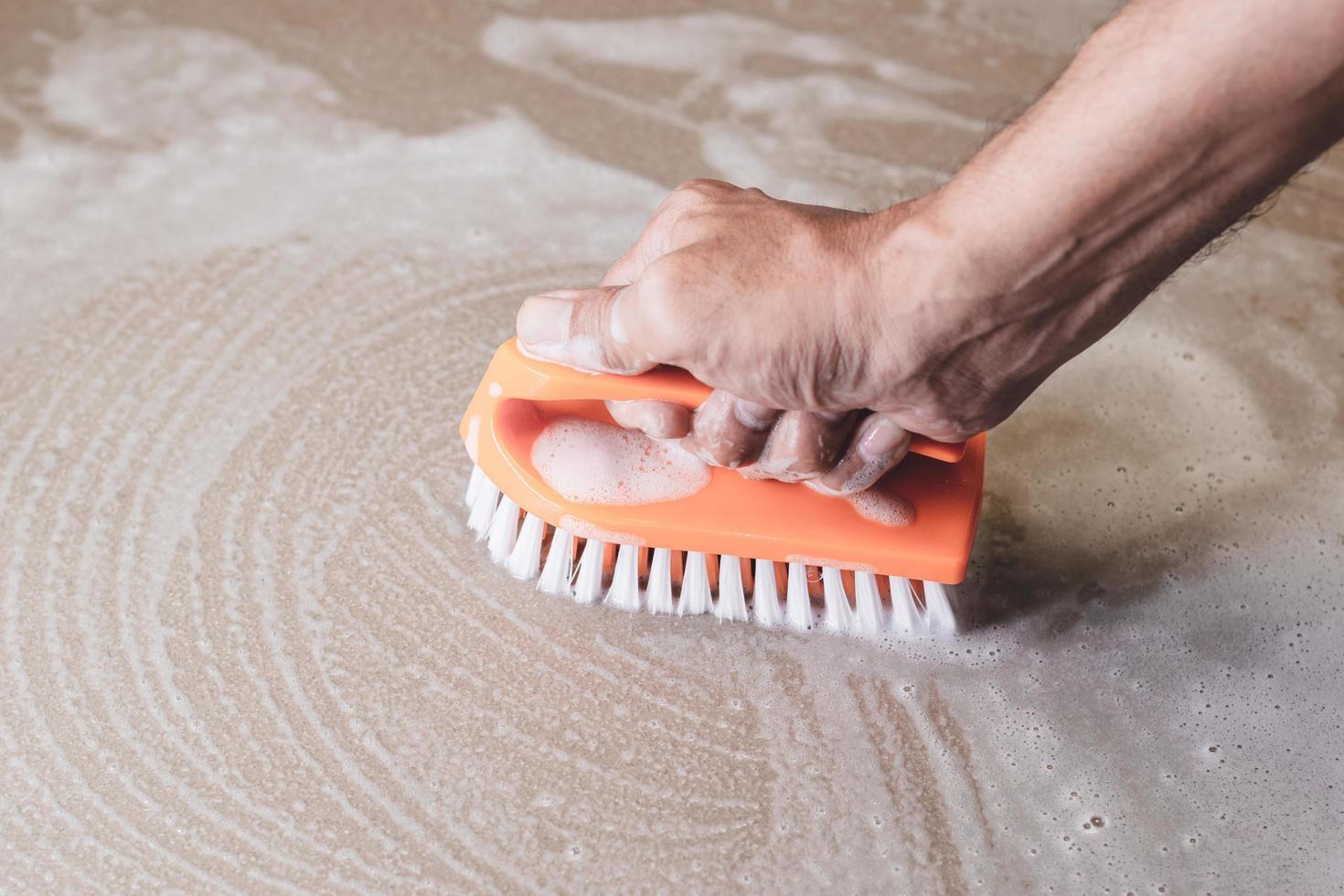 Nahaufnahme der Person, die einen Boden schrubbt foto