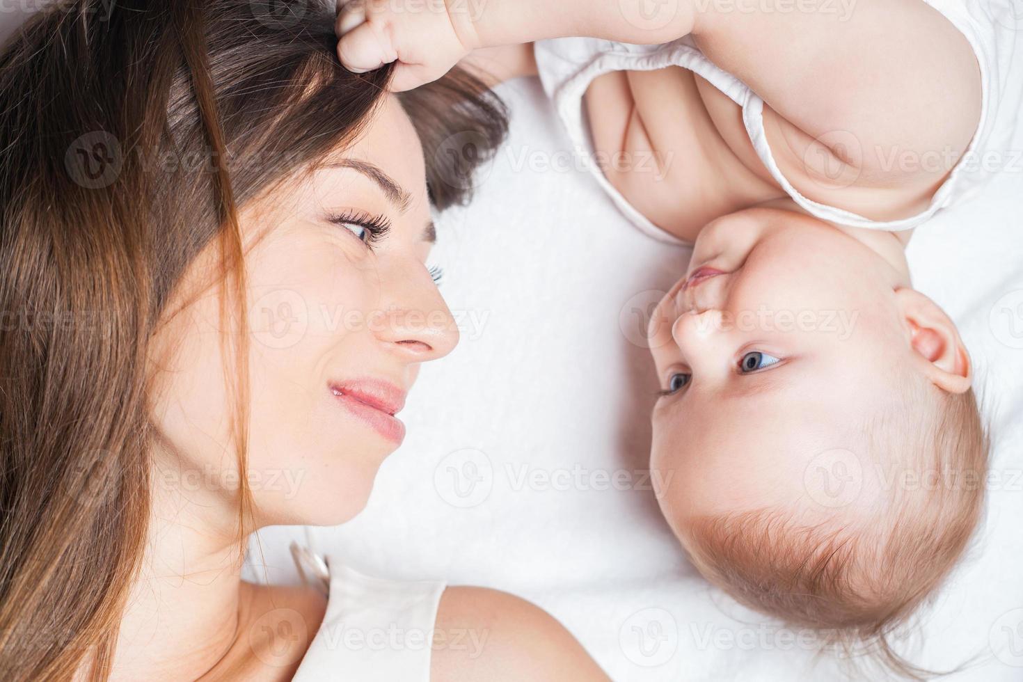 glückliche Mutter mit einem Baby, das auf einem weißen Bett liegt foto
