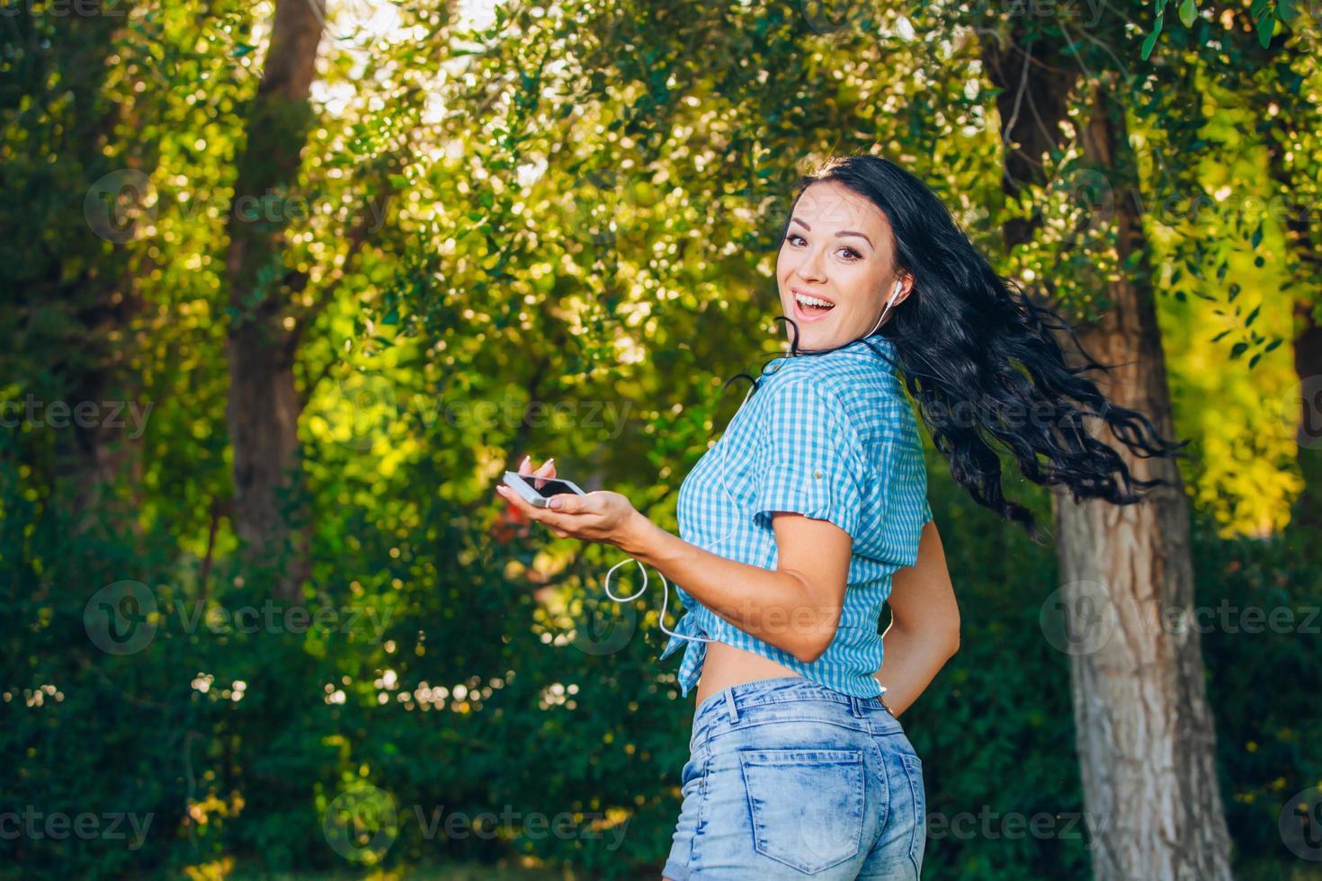 stilvolles schönes Mädchen des jungen Hipsters, das Musik, Handy hört foto