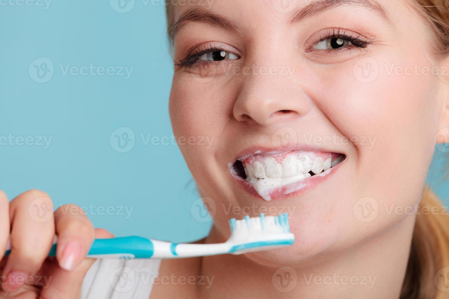 Frau mit Zahnbürste putzen Zähne putzen foto
