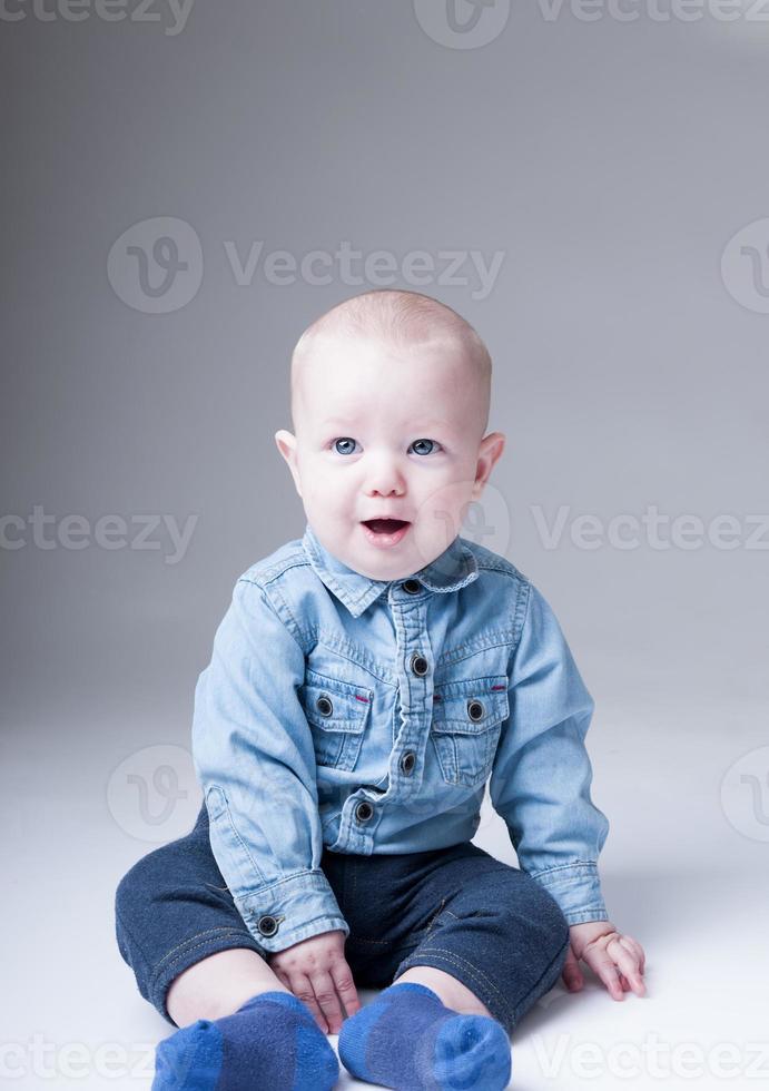 überraschter kleiner Junge im Jeanshemd foto