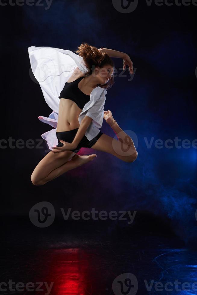 schöne junge Tänzerin, die auf Studiohintergrund aufwirft foto