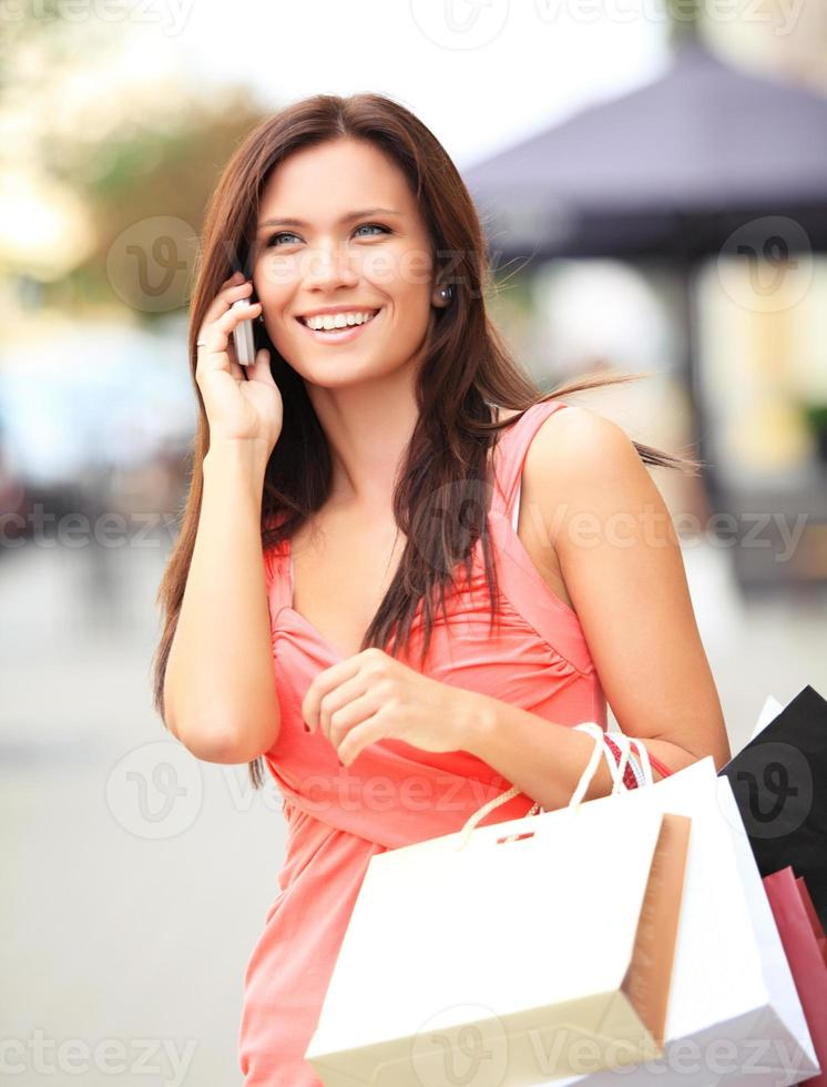 glückliche Frau, die Einkaufstaschen hält und Handy benutzt foto
