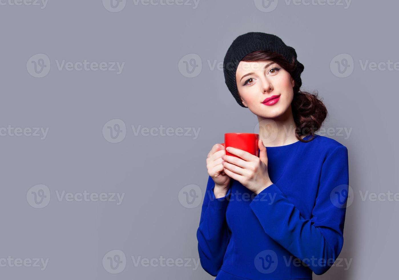 Frauen im blauen Kleid mit roter Tasse foto