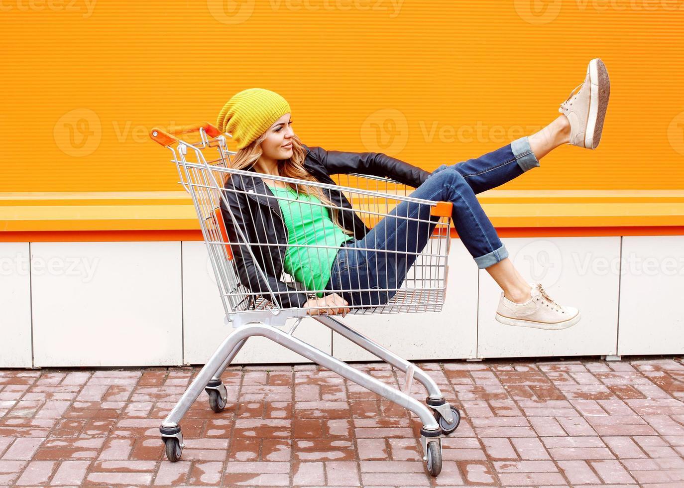 Modefrau reiten, die Spaß im Einkaufswagenwagen hat foto