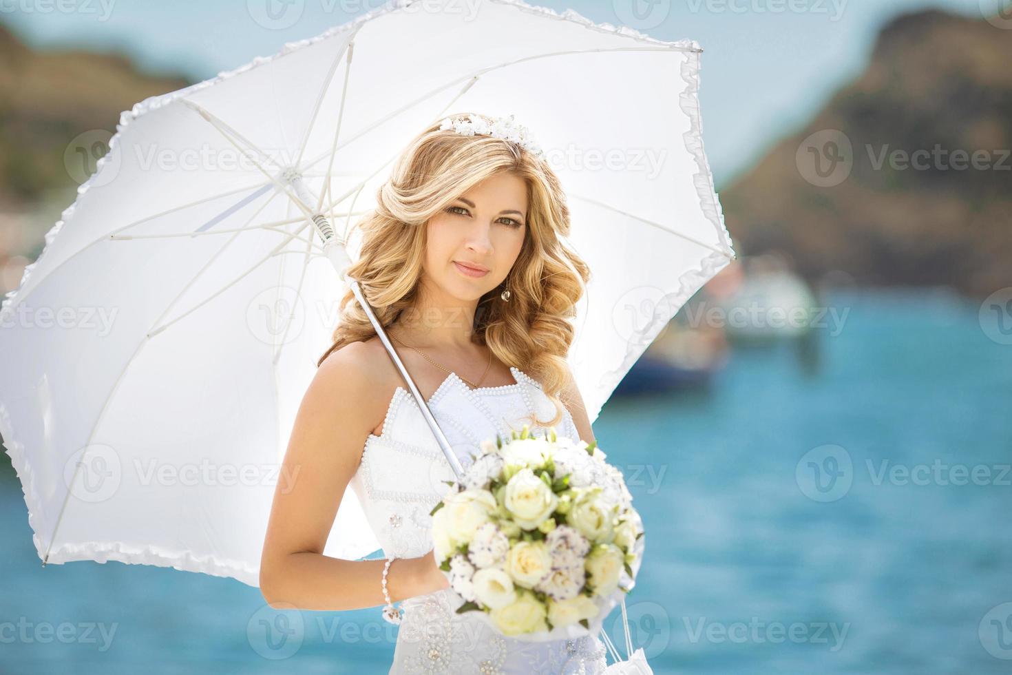 schönes Brautmädchen im Hochzeitskleid mit weißem Regenschirm foto