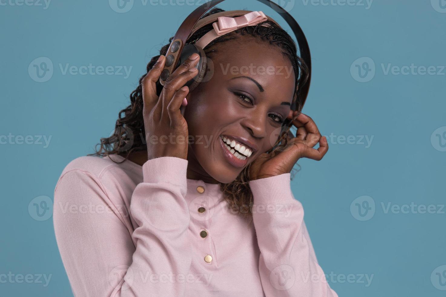 glückliche afrikanische Frau, die Musik über Kopfhörer hört. foto