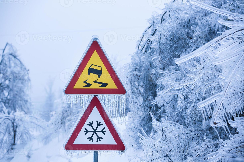 gefährliche und vereiste Straße mit schneereichen Bäumen foto