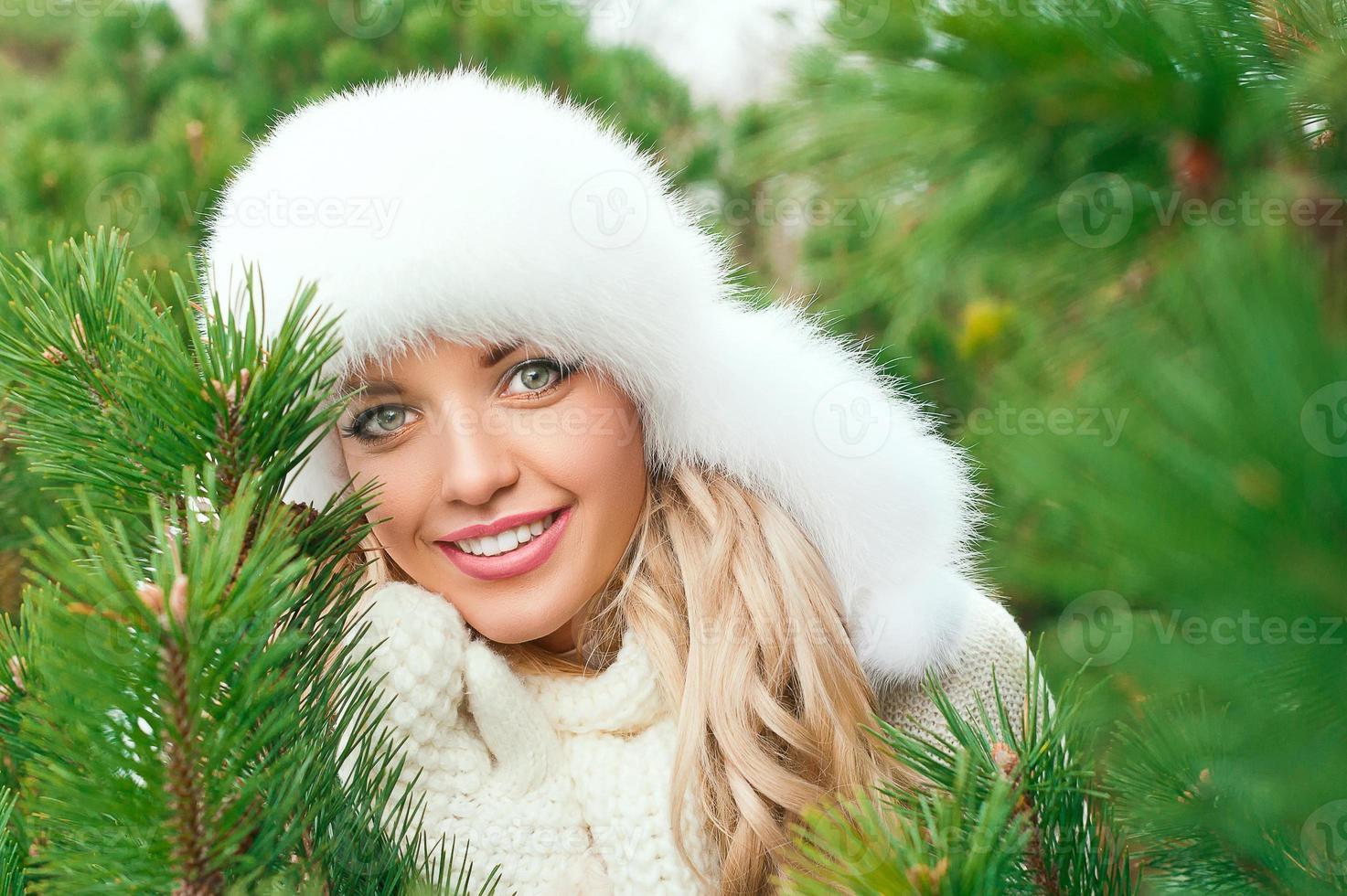 Frau im Hut, Fäustlinge, Schals, Pullover im Winterwald foto