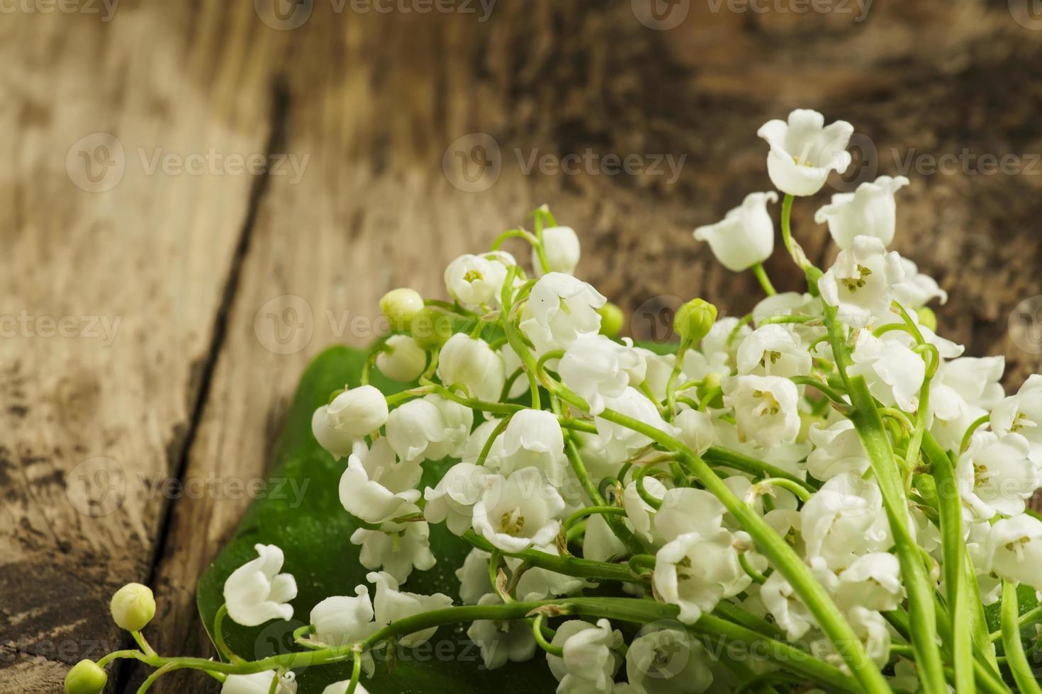 schöne Holzlilien des Tals auf einem Holztisch foto