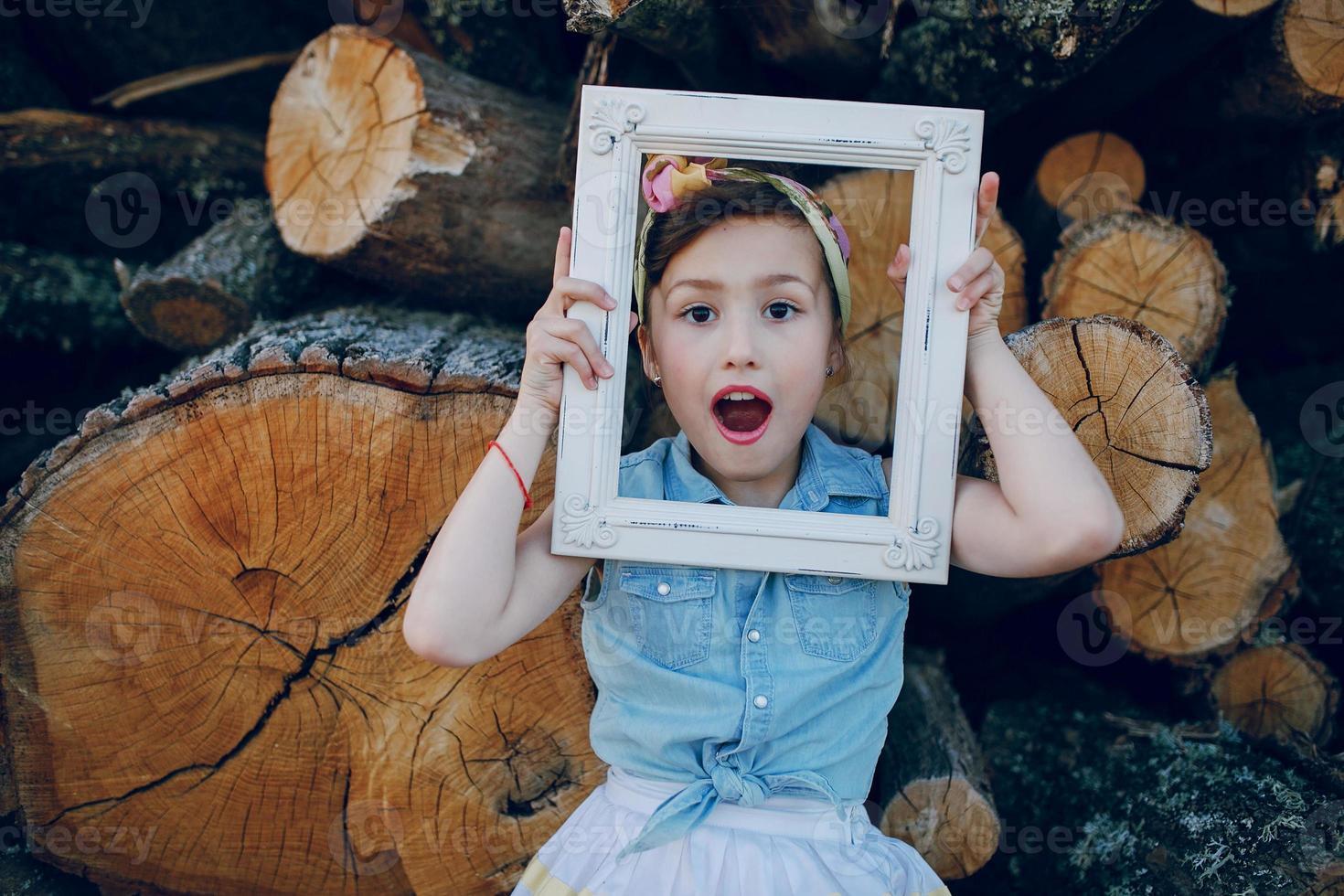 schönes kleines Mädchen, das auf Bäumen sitzt foto