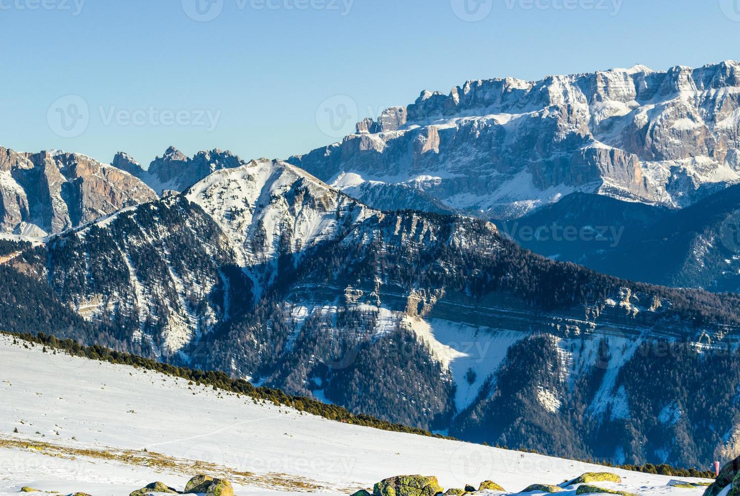 Panorama der Dolomiten mit schneebedeckten Gipfeln und Nadelbäumen foto