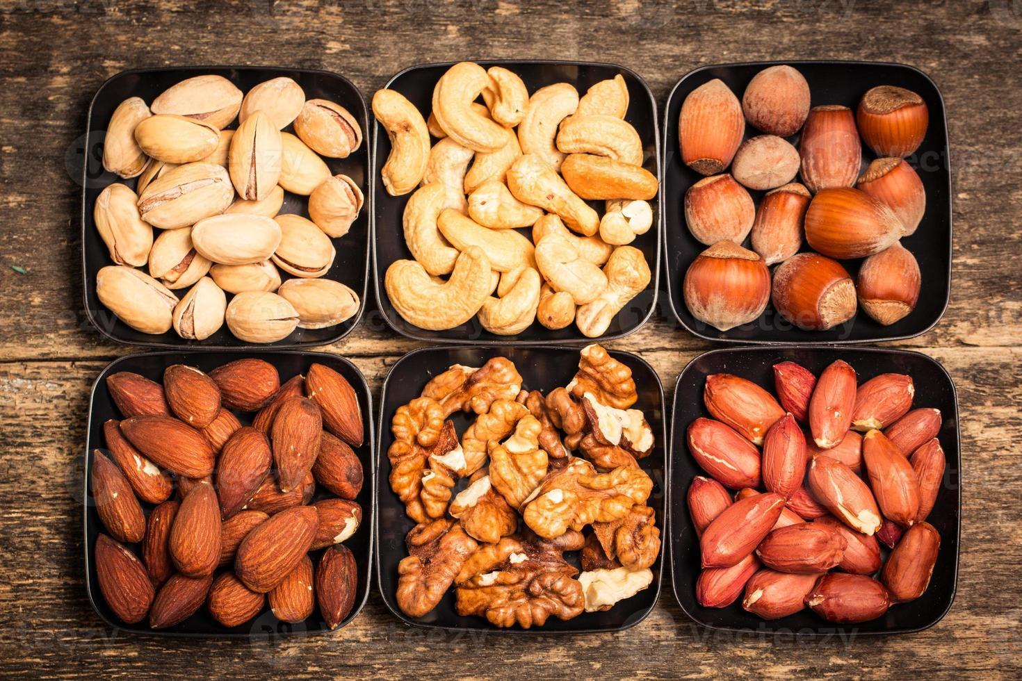 Nüsse auf Holztisch mischen, gesundes veganes Essen. foto