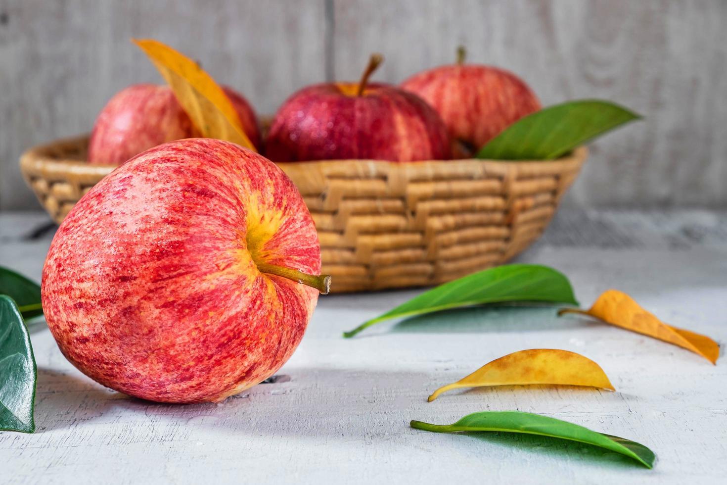 rote Äpfel auf einem weißen Holztisch foto