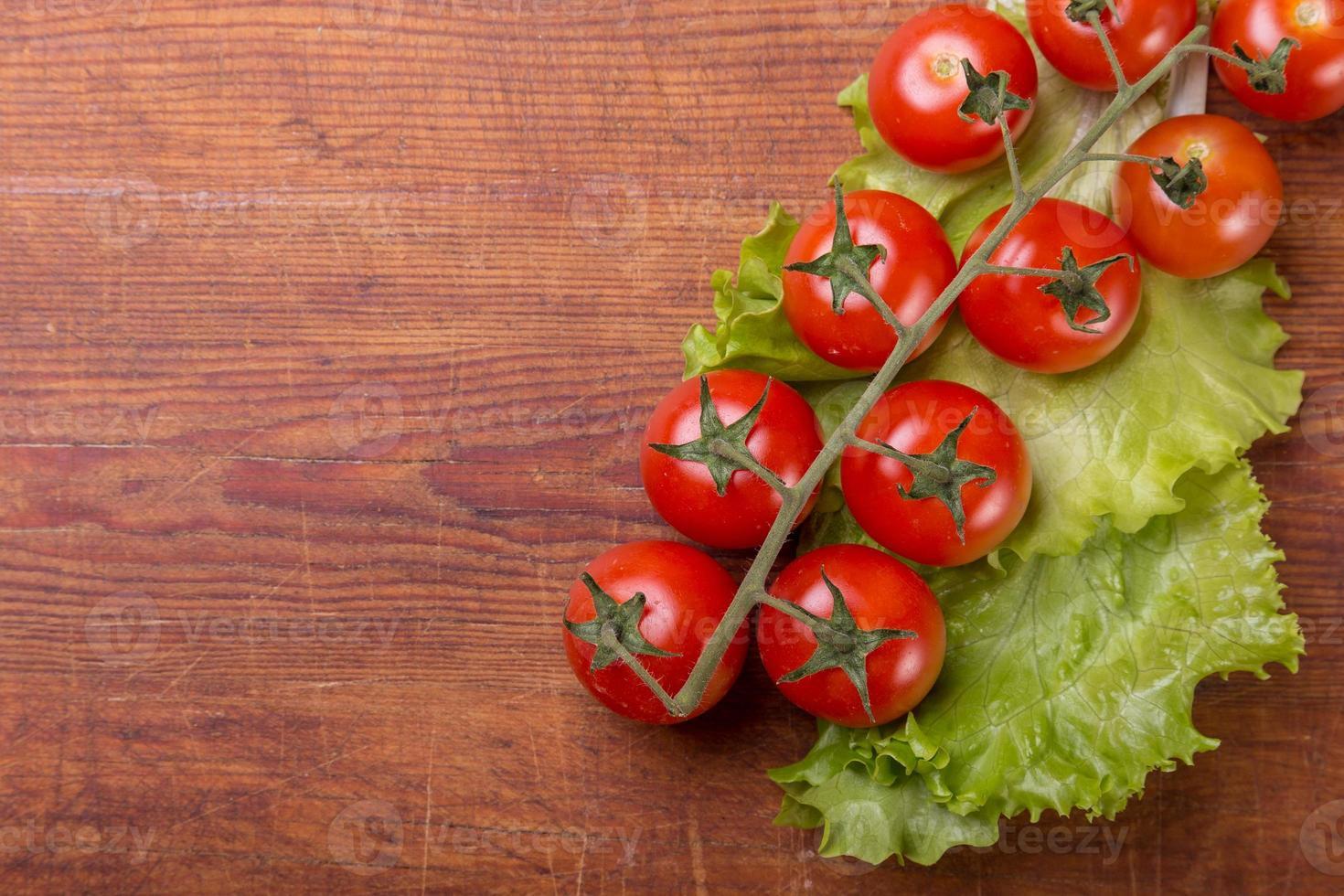 Tomatenzweig auf Vintage Holztisch foto