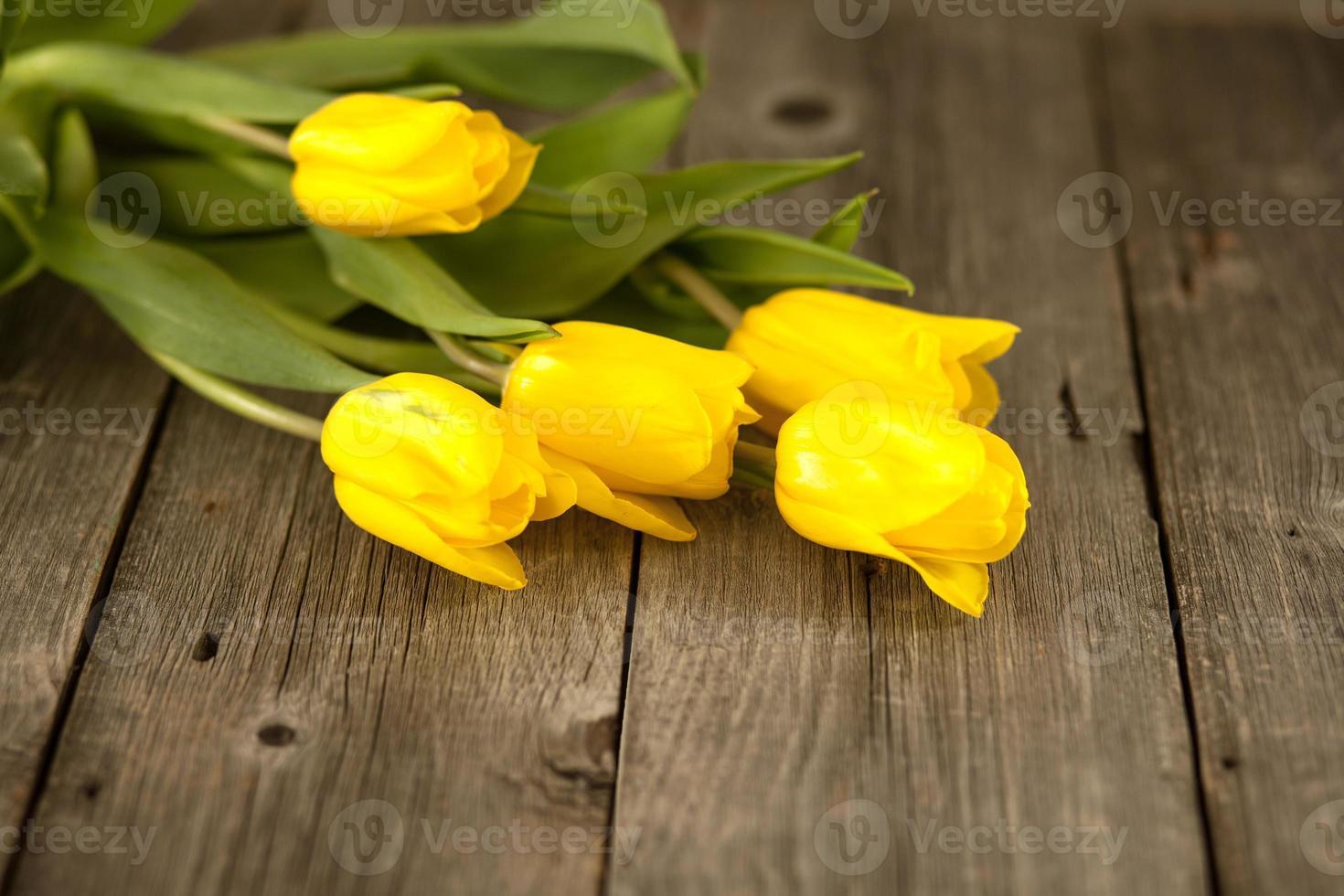 gelbe Tulpen auf einer Holzoberfläche foto