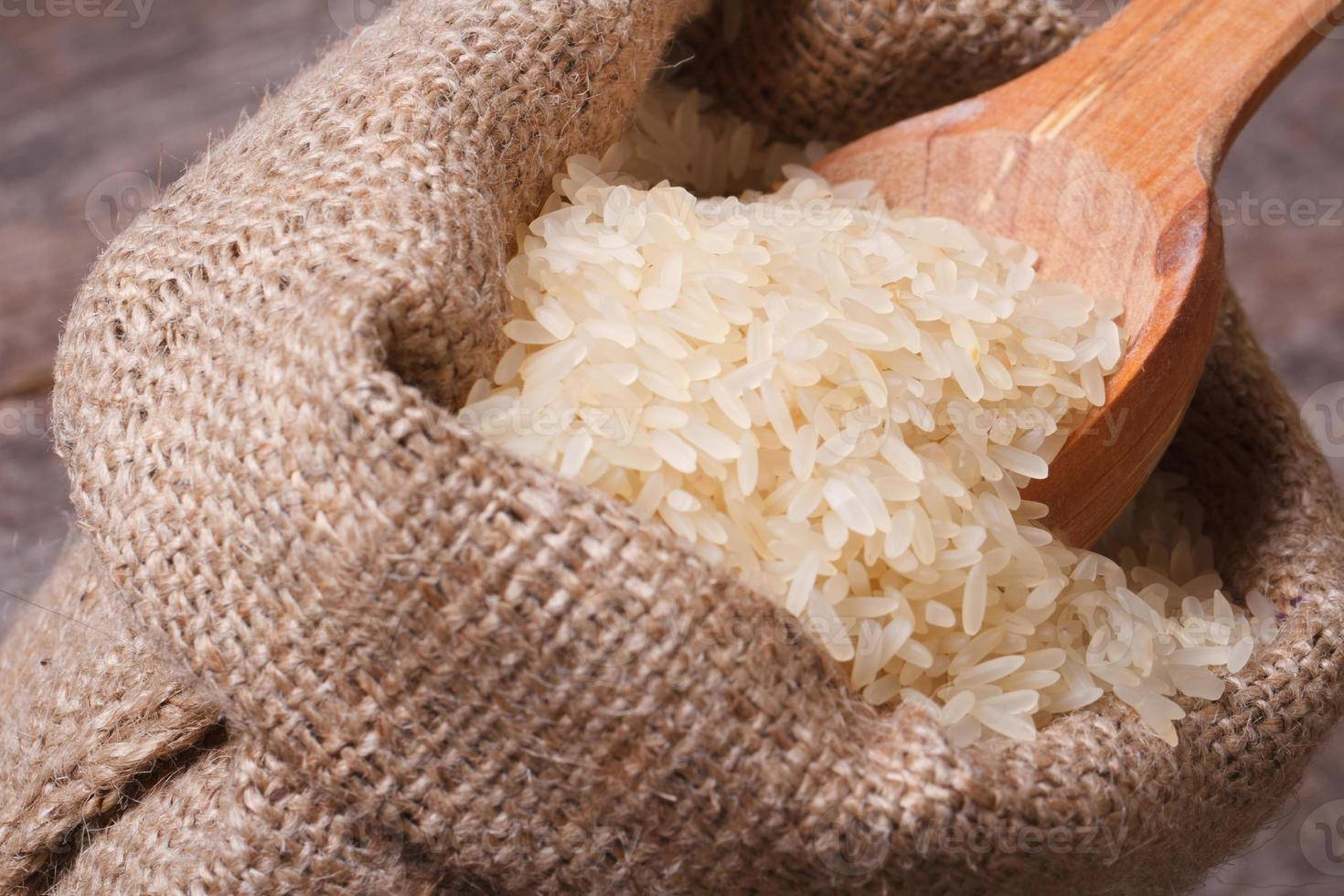 langer trockener Reis auf Holzlöffelmakro im Sack foto