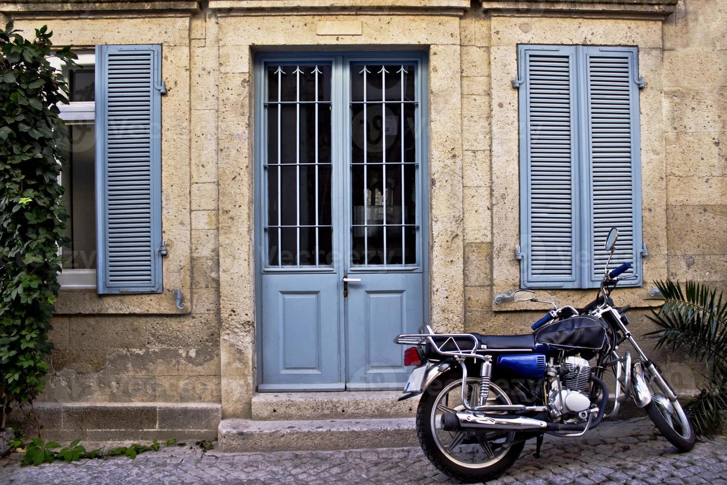 Steinhaus vor einem Motorrad foto