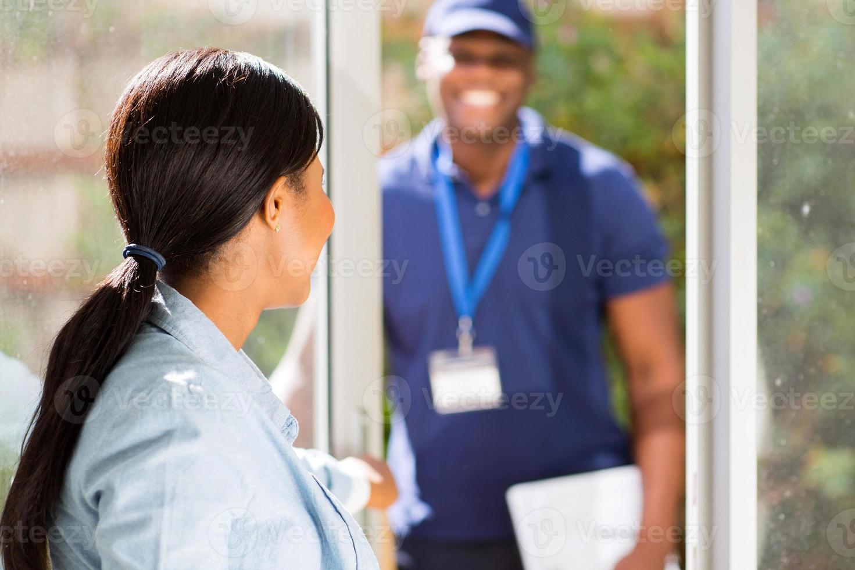 afrikanische Frau öffnet Tür Lieferbote foto