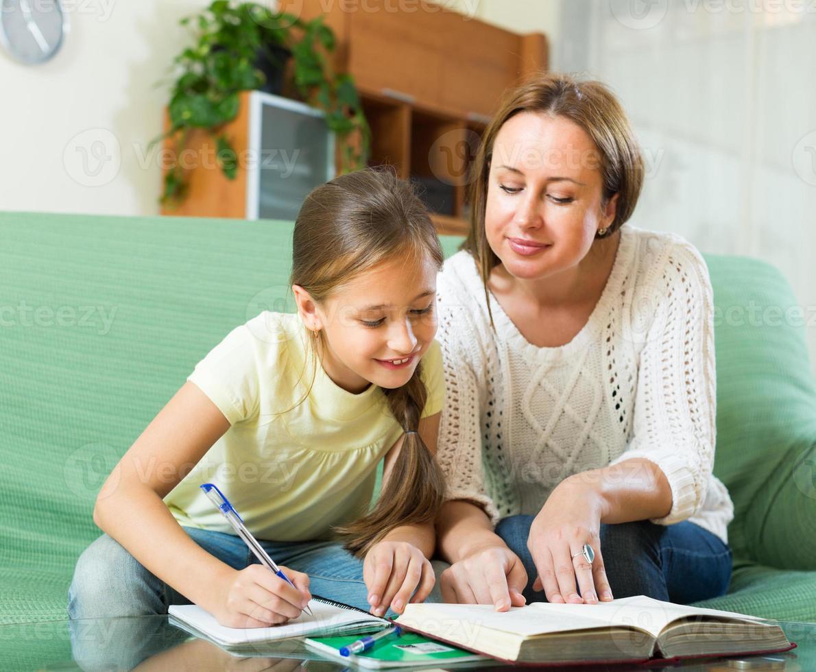 Schulmädchen und Mutter machen Hausaufgaben foto