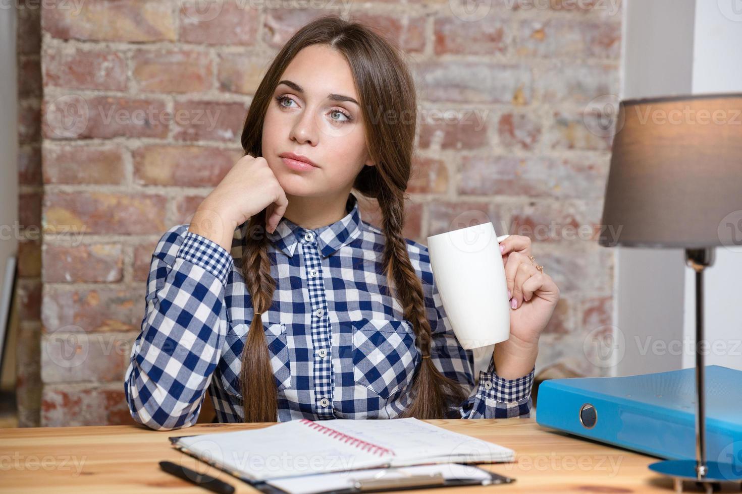 Studentin, die über ihre Hausaufgaben nachdenkt foto