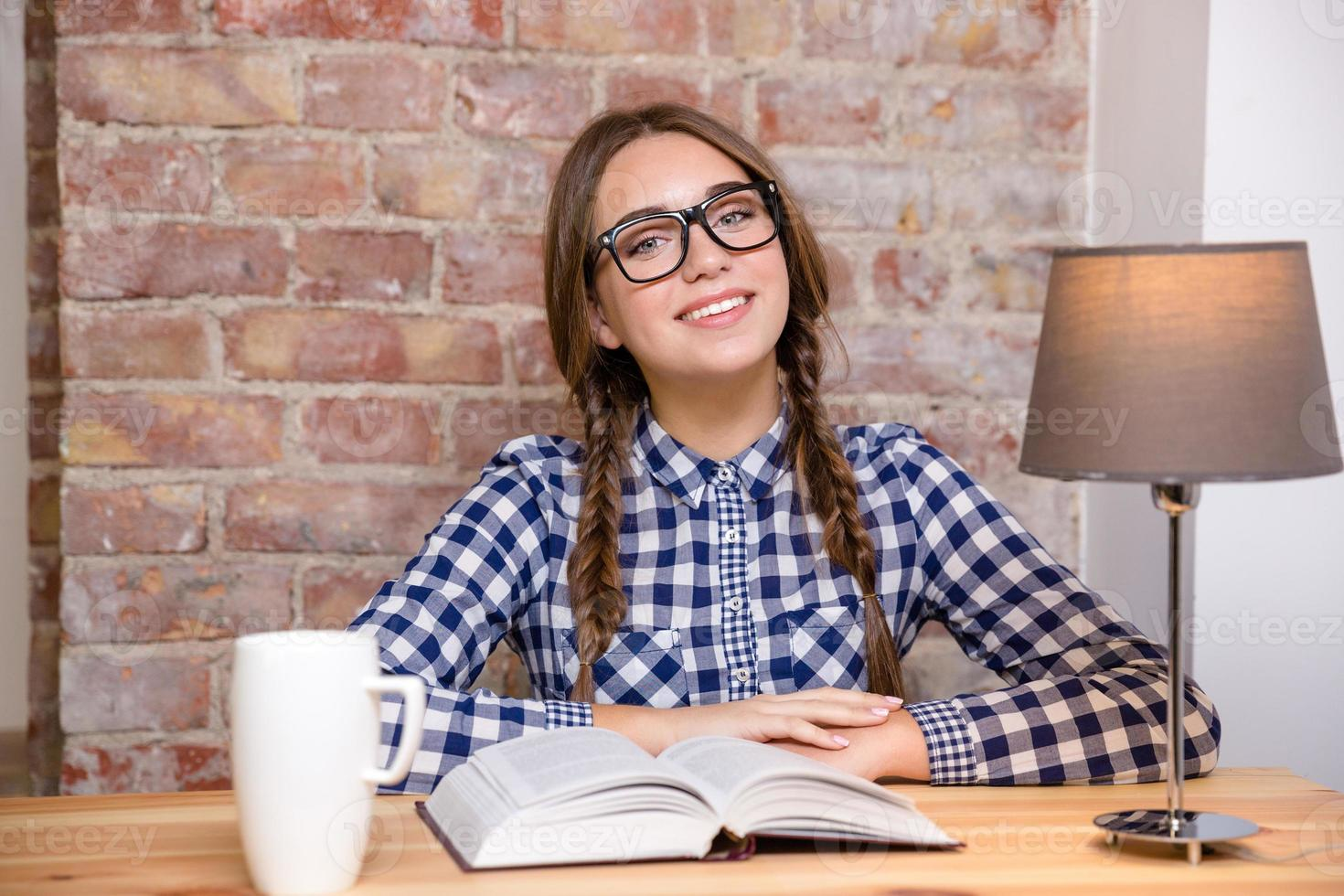 glückliche Frau in den Gläsern, die am Tisch mit Buch sitzen foto