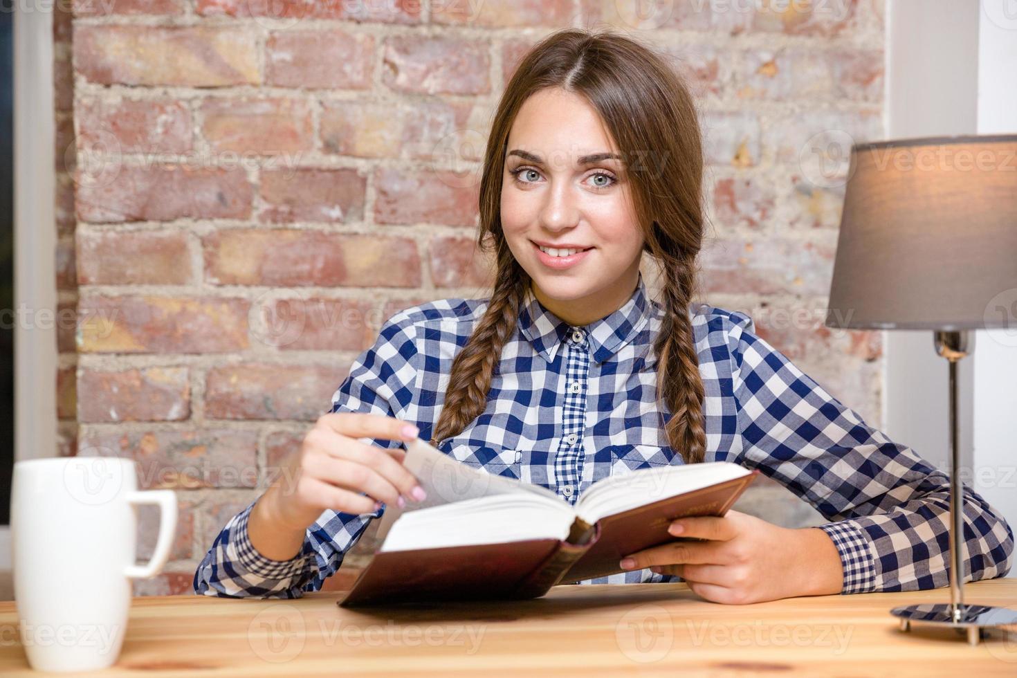 lächelnde Frau, die mit Buch am Tisch sitzt foto