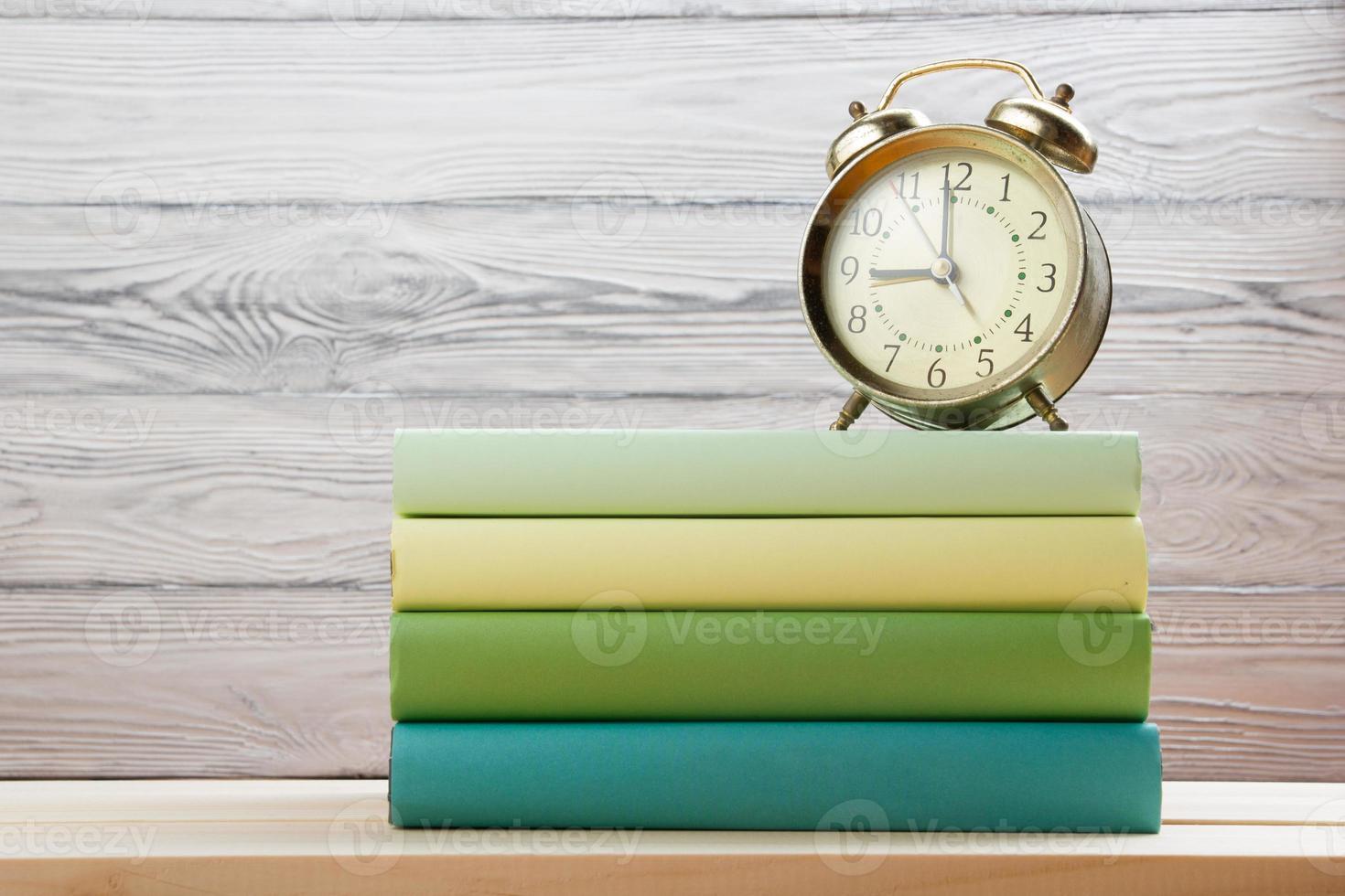 Stapel bunte Bücher und Wecker auf Holztisch. foto