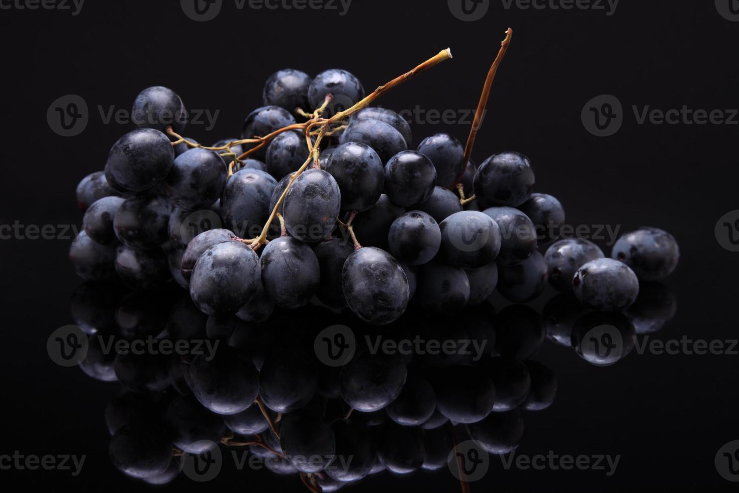 Bild der schwarzen Trauben auf schwarzem Hintergrund mit Reflexion foto