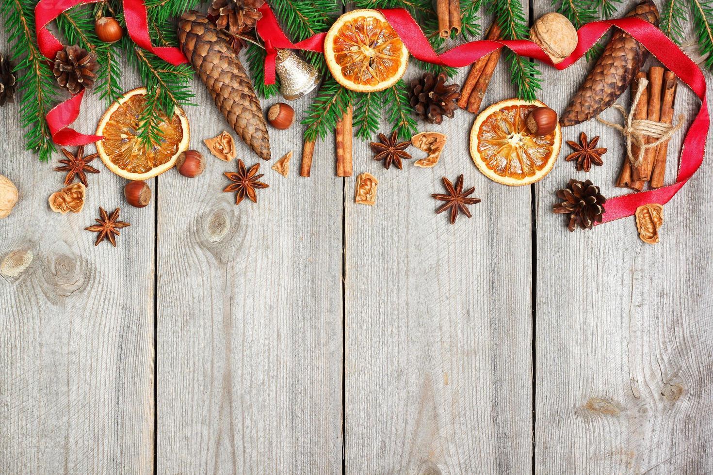 Weihnachtsdekoration mit Tannenbaum, Orangen, Zapfen, Gewürzen foto